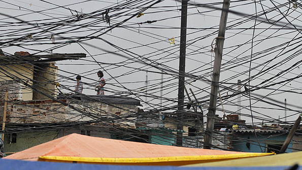 Tangled overhead electric power cables are pictured at a residential area as children stand on the roof of a house in Noida